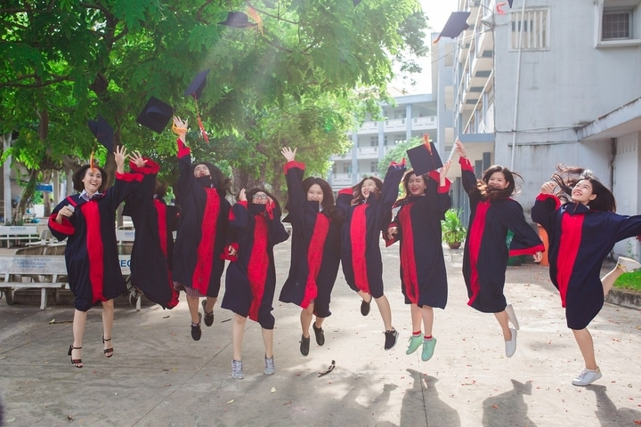 Excited university students throwing their caps after graduating